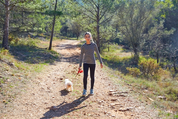 Tienermeisje die met een witte hond in bos lopen