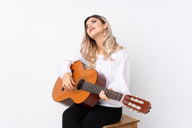 Tienermeisje die met gitaar over geïsoleerd wit omhoog terwijl het glimlachen kijken