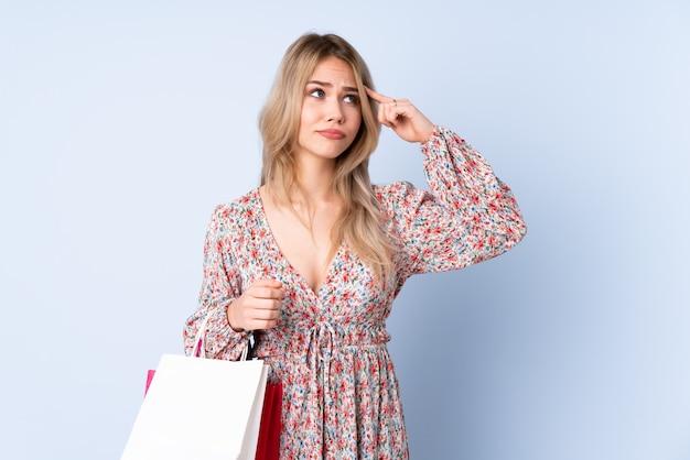 Tienermeisje die met het winkelen zak op blauwe muur het gebaar van waanzin maken die vinger op het hoofd zetten