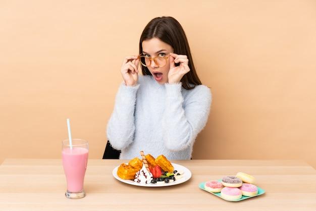 Tienermeisje die op beige muur met glazen wordt geïsoleerd die wafels eet en verrast die