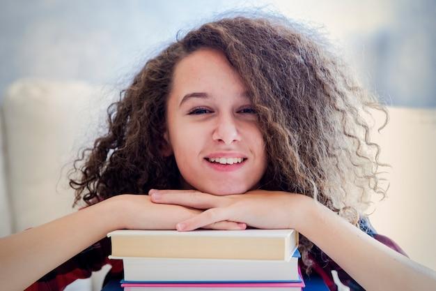 Tienermeisje die op boeken rusten