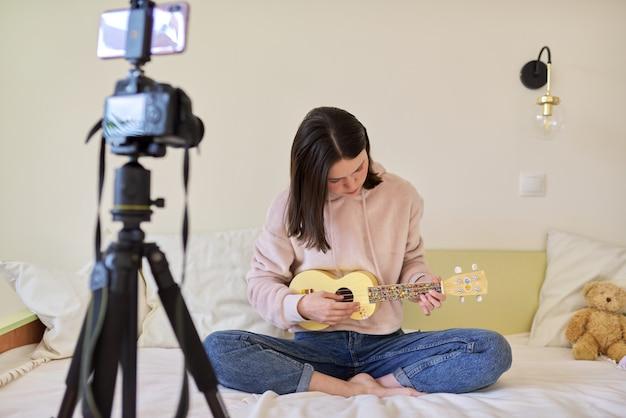 Tienermeisje die op ukelele spelen. blog, muziekkanaal, vlog, meisje dat online studeert, met volgers praat en muziek speelt