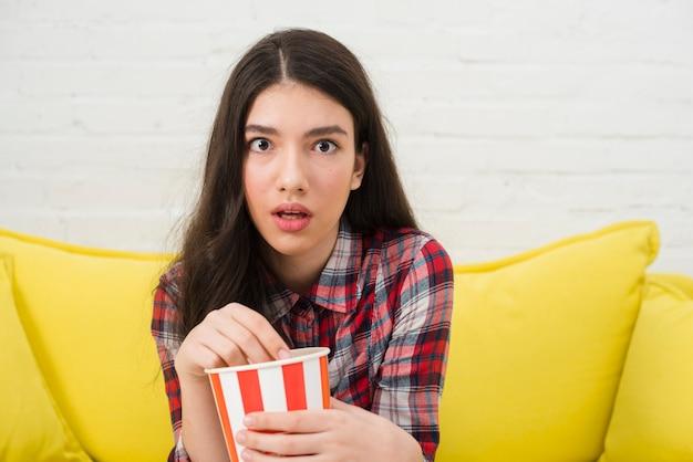 Tienermeisje die popcorn eten