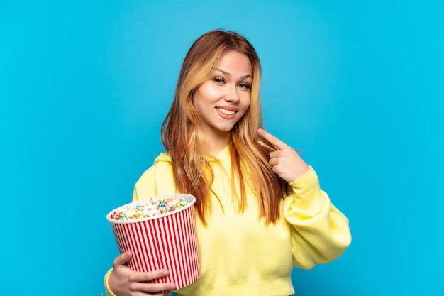 Tienermeisje die popcorns over geïsoleerde blauwe achtergrond houden die een duim omhoog gebaar geven