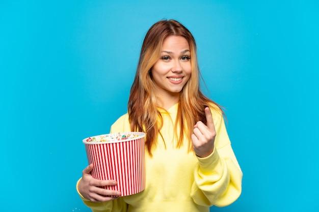 Tienermeisje die popcorns over geïsoleerde blauwe achtergrond houden die komend gebaar doen