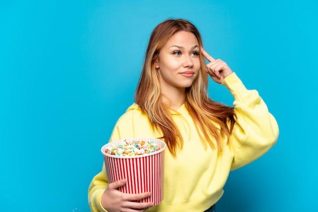 Tienermeisje die popcorns over geïsoleerde blauwe achtergrond houden die twijfels hebben en denken