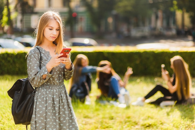 Tienermeisje die smartphone in park gebruiken