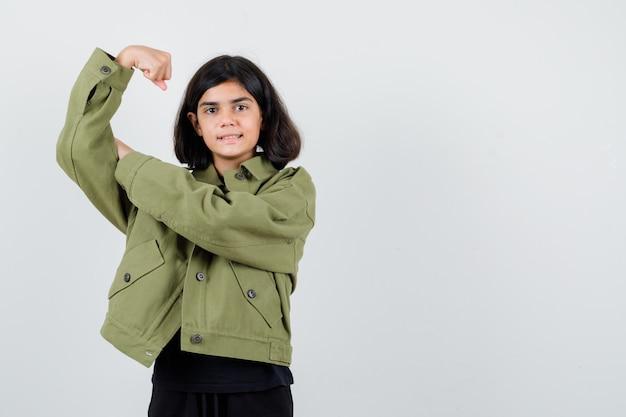 Tienermeisje die spieren van wapen in t-shirt, groen jasje tonen en vrolijk, vooraanzicht kijken.