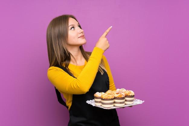 Tienermeisje die veel verschillende minicakes over geïsoleerde purpere muur houden die met de wijsvinger een groot idee richten