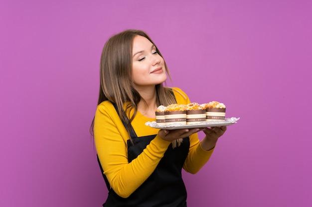 Tienermeisje die veel verschillende minicakes over geïsoleerde purple houden