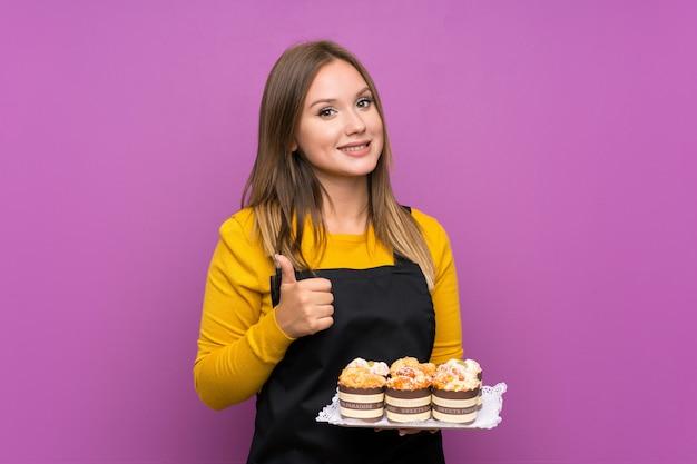 Tienermeisje die veel verschillende minicakes over het geïsoleerde purper geven houden duimen op gebaar