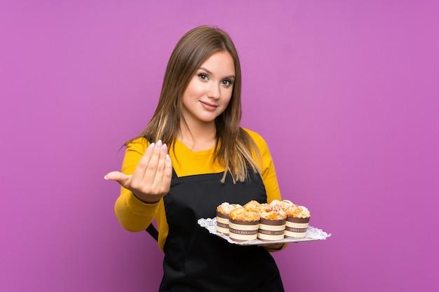 Tienermeisje die veel verschillende minicakes over het geïsoleerde uitnodigen houden te komen