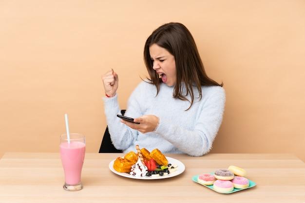 Tienermeisje die wafels eten die op beige muur met telefoon in overwinningspositie worden geïsoleerd