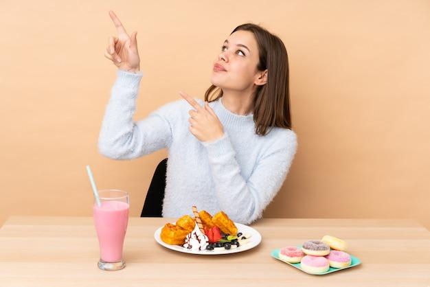 Tienermeisje die wafels eten die op beige muur worden geïsoleerd die met de wijsvinger een groot idee richten