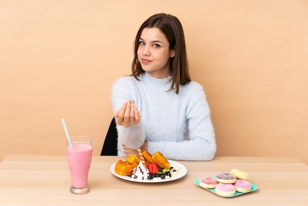 Tienermeisje die wafels eten die op beige muur worden geïsoleerd die met hand uitnodigen te komen. blij dat je bent gekomen