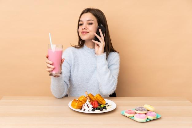 Tienermeisje die wafels eten die op de beige koffie van de muurholding worden geïsoleerd om weg te halen en mobiel