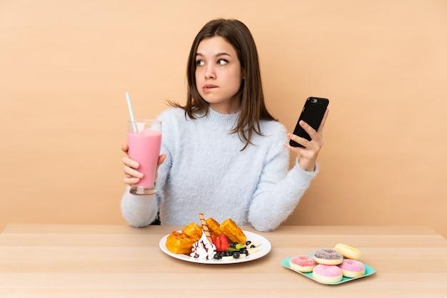 Tienermeisje die wafels op de beige weg te nemen koffie van de muurholding en mobiel eten terwijl het denken van iets