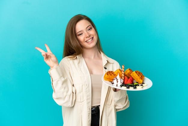 Tienermeisje die wafels over geïsoleerde blauwe achtergrond houden die glimlachen en overwinningsteken tonen