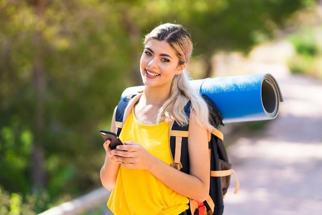 Tienermeisje die wandelen in openlucht bij het verzenden van een bericht met mobiel