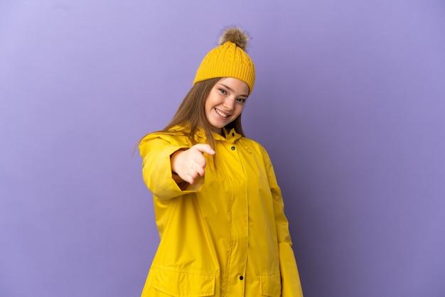Tienermeisje draagt een regenbestendige jas over geïsoleerde paarse achtergrond en schudt handen voor het sluiten van een goede deal