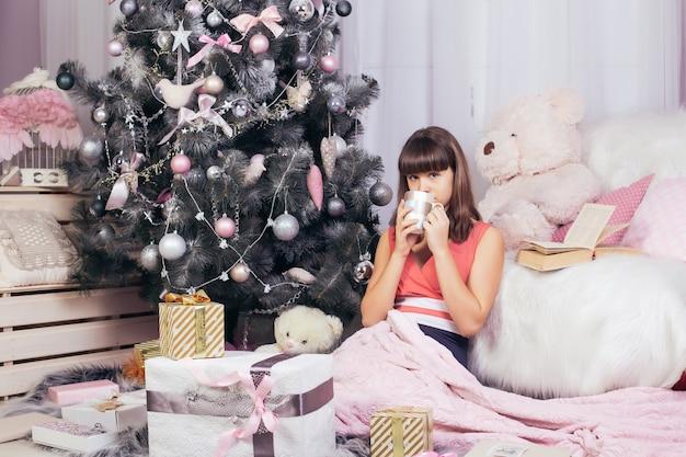 Tienermeisje drinkt thee in de woonkamer van het nieuwe jaar, omringd door cadeaus en speelgoed, naast de kerstboom.