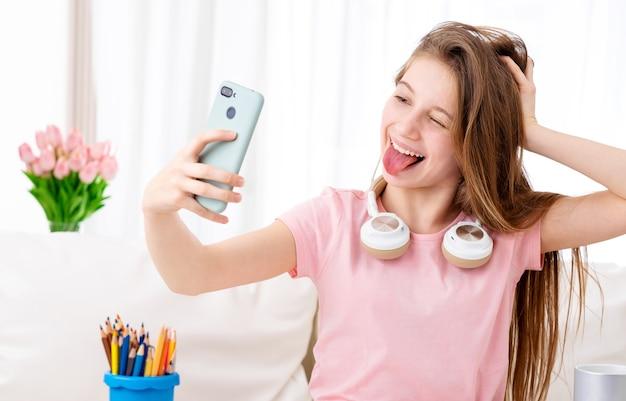 Tienermeisje een selfie nemen terwijl het dragen van een koptelefoon