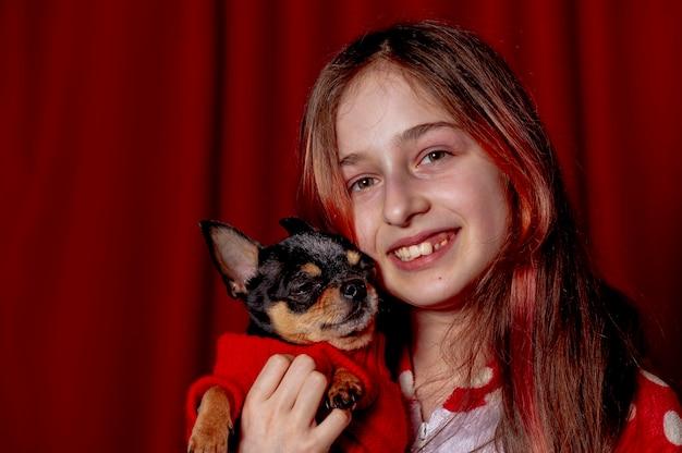 Tienermeisje en een chihuahua gekleed in een rode trui voor honden thuis tegen een achtergrond van rood.