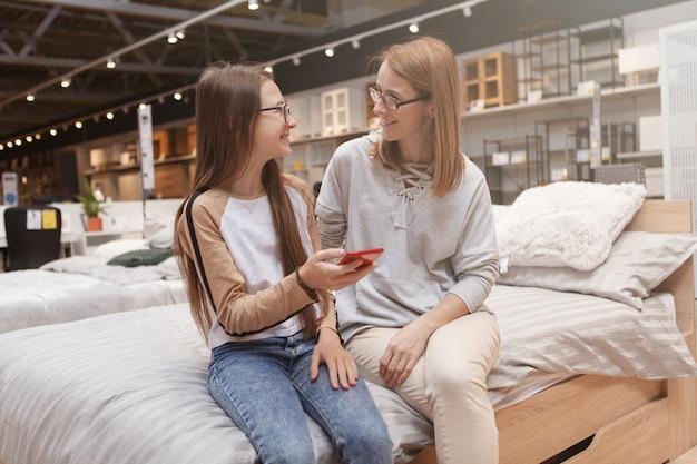 Tienermeisje en haar moeder praten tijdens het samen gebruik van slimme telefoon