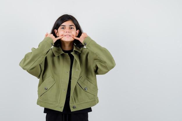 Tienermeisje forceert een glimlach op het gezicht in t-shirt, groene jas en kijkt gefocust, vooraanzicht.