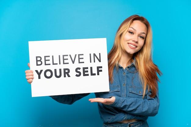Tienermeisje geïsoleerd met een bordje met de tekst believe in your self en erop wijzend