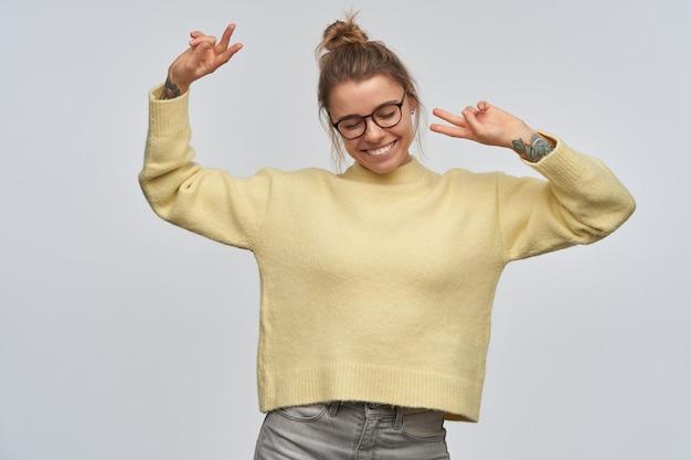 Tienermeisje, gelukkig uitziende vrouw met blond haar verzameld in een broodje en tatoeages. gele trui en bril dragen. houdt haar armen omhoog en toont vredestekens. dansen geïsoleerd over witte muur