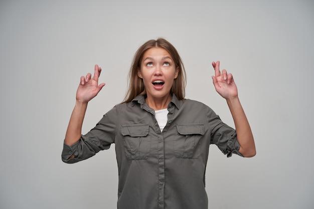 Tienermeisje, gelukkig uitziende vrouw met bruin lang haar. ze draagt een grijs shirt en houdt haar vingers gekruist, een wens doen, vragen. kijken naar kopieerruimte, geïsoleerd over grijze achtergrond