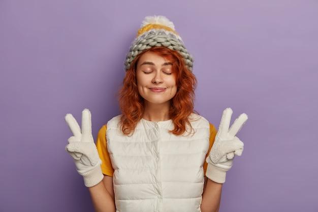Tienermeisje geniet van wintertijd, maakt overwinning handgebaar, draagt sneeuwwit vest en handschoenen, gebreide muts, heeft gember haar, sluit ogen