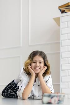 Tienermeisje glimlachend liggend op de vloer en kijken naar online uitzending in smartphone, online training