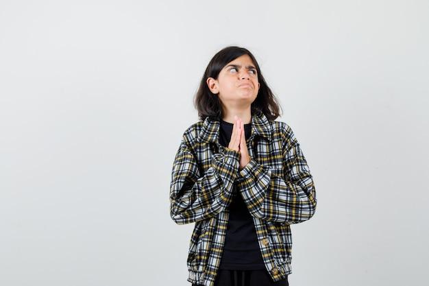 Tienermeisje hand in hand in biddend gebaar, opzij kijkend in casual shirt en boos kijken. vooraanzicht.