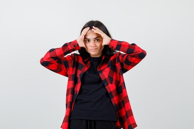 Tienermeisje hand in hand in de buurt van gezicht in t-shirt, geruit hemd en ziet er tevreden uit, vooraanzicht.
