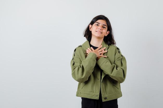 Tienermeisje hand in hand op borst in groene jas en ziet er gelukkig uit, vooraanzicht.