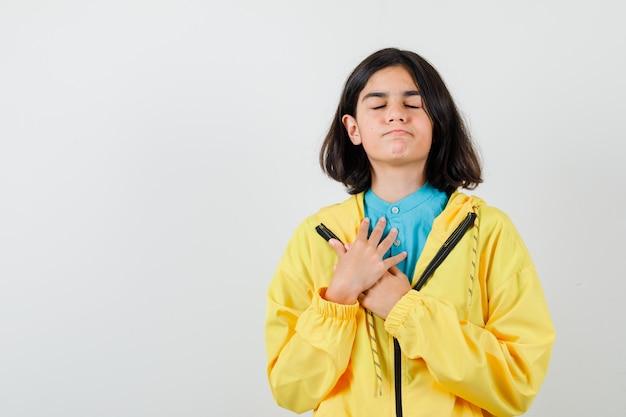 Tienermeisje hand in hand op de borst in gele jas en ziet er dromerig uit. vooraanzicht.