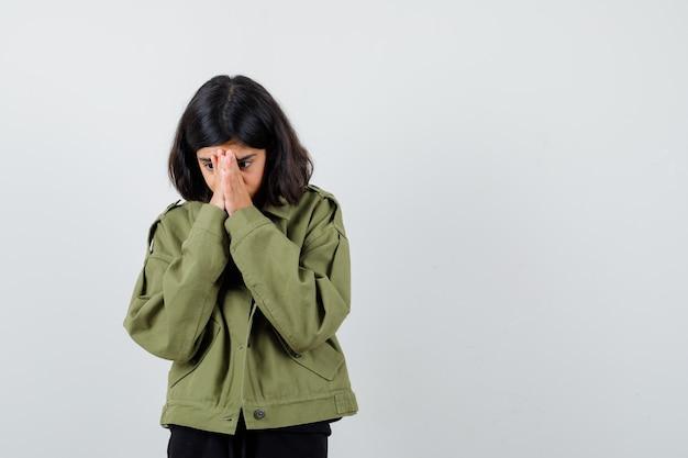 Tienermeisje hand in hand op gezicht in t-shirt, groen jasje en peinzend kijkend. vooraanzicht.