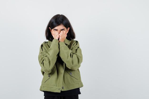 Tienermeisje hand in hand op mond in t-shirt, groene jas en verward kijken. vooraanzicht.