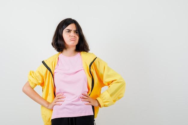 Tienermeisje hand in hand op taille in geel trainingspak, t-shirt en kijkt bedroefd, vooraanzicht.