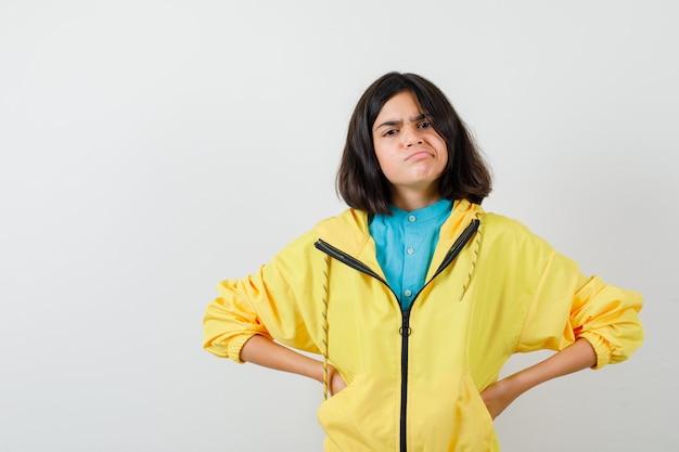 Tienermeisje hand in hand op taille terwijl ze fronst in gele jas en verward kijkt, vooraanzicht.