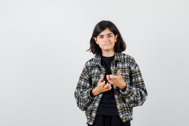 Tienermeisje hand in hand voor zichzelf in casual shirt en aarzelend, vooraanzicht.