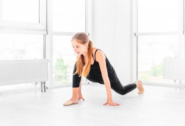 Tienermeisje het uitrekken zich in oefenruimte