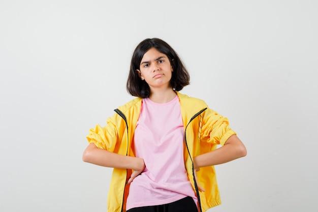 Tienermeisje houdt armen op taille in t-shirt, jas en kijkt peinzend. vooraanzicht.
