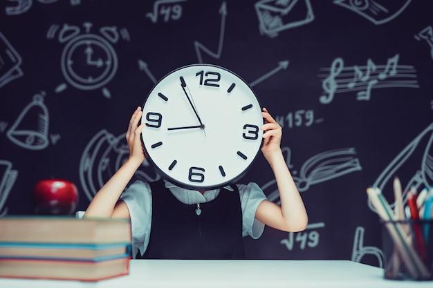 Tienermeisje houdt een grote klok in haar handen, horloge bedekt haar gezicht