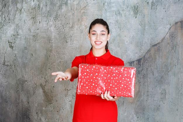 Tienermeisje houdt een rode geschenkdoos met witte stippen erop en nodigt iemand naast haar uit.