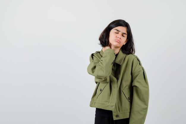 Tienermeisje houdt hand achter nek in t-shirt, jas en ziet er pijnlijk uit. vooraanzicht.
