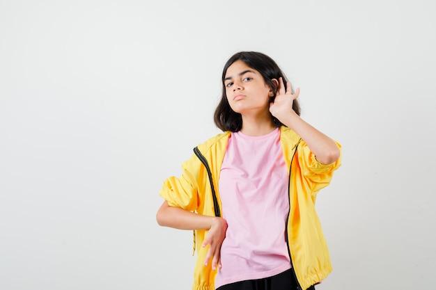 Tienermeisje houdt hand achter oor, houdt hand op taille in t-shirt, jas en kijkt gefocust. vooraanzicht.