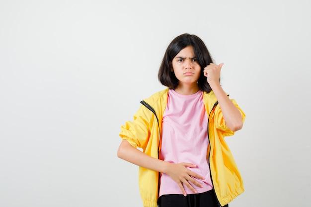 Tienermeisje houdt hand op de buik, wijst terug met duim in t-shirt, jas en kijkt geïrriteerd. vooraanzicht.